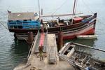 aus einer arabischen Dau im altem Hafen von Mobasa wird Trockenfisch entladen