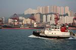Containerschiff und Schlepper im Hafen von Hongkong vor Hochhäusern