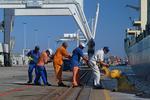 Hafenarbeiter in Kapstadt ziehen die Festmacherleine im Port of Cape Town, Südafrika