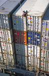 Lascher in Vancouver mit Laschstange löst die Twistlocks  auf dem Containerschiff im Port of Vancouver, Canada