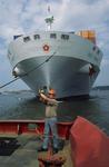 Bootsmann auf dem Schlepper gibt dem Schlepperkapitän das Zeichen, dass die Abschleppleine fest ist