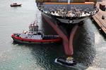 Festmacher am Bug des Containerschiffs holt die Festmacherleine während der Schlepper das Schiff zum Kai drückt