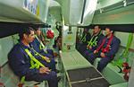 Seeleute warten im Rettungsboot (Freifallboot) auf das Ausklinken vom Schiff, Sicherheitsübung, Rettungsübung