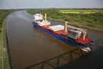 Nord-Ostsee-Kanal (Kiel Canal) mit Feederschiff SUDEROOG und Rapsfeld