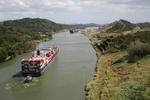 Die engste Strecke des Panamakanals, der Corte Gaillard, hinten die Pedro Miguel Schleuse und die Hochhäuser von Panama City