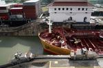 Panamakanal, Panama Canal (Canal de Panama), die Schleusenlokomotive hält das Containerschiff auf Abstand zu den Schleusenwänden