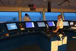 Kapitän auf der Schiffsbrücke abends mit der Hand am Maschinentelegraf (Fahrstufenregler)