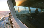 Offizier mit Fernglas auf der Schiffsbrücke mit Spiegelung der Abendsonne