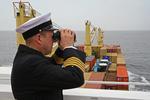 Kapitän mit Fernglas auf der Brückennock des Containerschiffs