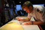 Offizier zeichnet die Fahrtroute in die Seekarte