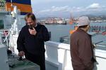 Kapitän und Lotse am Fahrstand auf der Brückennock dirigieren das Contanerschiff an den Kai vom Port of Busan