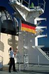 Seemann hisst die Deutschlandfahne vor der Einfahrt in den Hafen