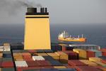 Blick über die Container auf dem Mittelschiff zum Schornstein eines Großcontainerschiffs